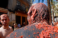 A man covered by tomato pulp seen during La Tomatina festival in Bunol, Spain, 31 August 2006. La Tomatina is a tomato fight held annually in the town of Bunol, close to Valencia. Approximately 40,000 people from all over the world arrive to fight in the battle in which about 50 tons of over-ripe tomatoes are thrown in the street. During the one hour battle everybody fights everybody by throwing squashed tomatoes. The origin of this event is unknown but the Tomatina fights have been recorded since 1945.