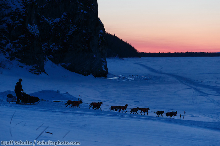 Ken Anderson runs down the bank onto the Yukon River as he leaves Ruby after sunset on Friday, March 7, during the Iditarod Sled Dog Race 2014.<br /> <br /> PHOTO (c) BY JEFF SCHULTZ/IditarodPhotos.com -- REPRODUCTION PROHIBITED WITHOUT PERMISSION