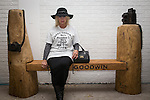 © Joel Goodman - 07973 332324 . 2 November 2013 . Chorlton Precinct (aka The Square ) Manchester , UK . STEPHANIE TRYHUBA (from Bury, correct - 07735 861661) , friend of Harry's , sits on the bench wearing a t-shirt dedicated to Harry . A bench in memory of photographer Harry Goodwin is unveiled at Chorlton Precinct . The locally created carved wood design features two cameras , one a historic twin-lens reflex design and the other a modern 35mm design . Photo credit : Joel Goodman