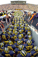 "The University of Michigan football team takes to the field at Michigan Stadium, ""The Big House"", in  Ann Arbor, MI."