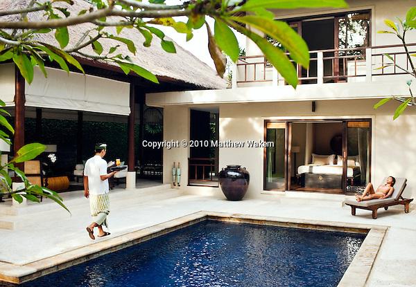 Woman relaxing by pool at the Kempli private pool villa, Kayumanis Gangsa, Bali, Indonesia.
