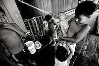 Iquitos, Peru, Jan. 11, 2007 - Johnny Basadre Pastor, 10, upper right, holds his sister, Nevia Basadre Pastor, 6 months, while his younger brother, Cesar 'Charlie' Basadre Pastor, fixes her socks on their porch in Belen, a small poverty-stricken area built along the flats of the Amazon River. Home to over 100,000 residents, the community is comprised of homes built on stilts or of floating balsa wood.  The children were all just came from a swim in the Amazon to beat the summer heat. As eldest child, Johnny is responsible for helping with his siblings while his father is out fishing and his mother works in the market.