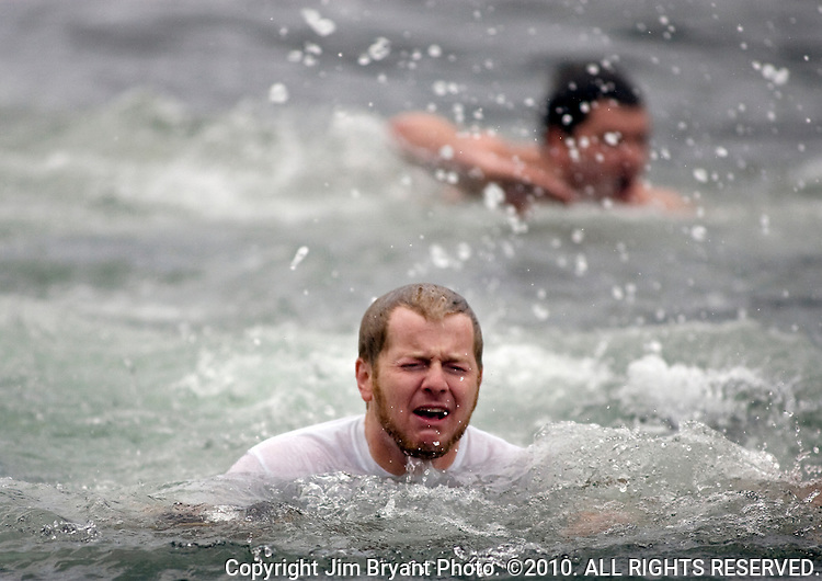 Sam Dupuis (L) swims to the shore after jumping into the Burley Lagoon during the 26th annual Polar Bear  in Olalla, Washington on 1 January  2010. Over 300 hardy participants  braved the chilly lagoon waters to join in on the annual New Year's Day Tradition.  Jim Bryant Photo. ©2010. ALL RIGHTS RESERVED.