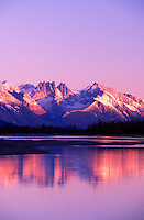 Alpenglow settles over mountains reflected in water. Tongass National Forest, Inside Passage, Alaska.