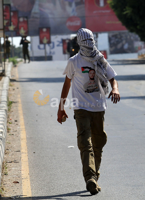A Palestinian protester carries stones towards Israeli troops during clashes following a protest in solidarity with Palestinian prisoners held in Israeli jails, at the Hawara checkpoint near the West Bank city of Nablus on Aug. 18, 2016. Photo by Nedal Eshtayah