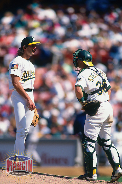 OAKLAND, CA - Dennis Eckersley and Terry Steinbach of the Oakland Athletics talk on the mound during a game at the Oakland Coliseum in Oakland, California in 1994. Photo by Brad Mangin