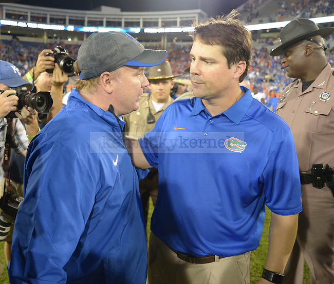 UK head coach Mark Stoops and Florida head coach Will Muschamp shake hands after the UK football game against Florida at Commonwealth Stadium in Lexington, Ky., on Saturday, September 28, 2013. Photo by Eleanor Hasken | Staff
