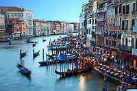 An early evening view from the Rialto Bridge. Gondolas move gracefully through the Grand Canal as the sun sets.