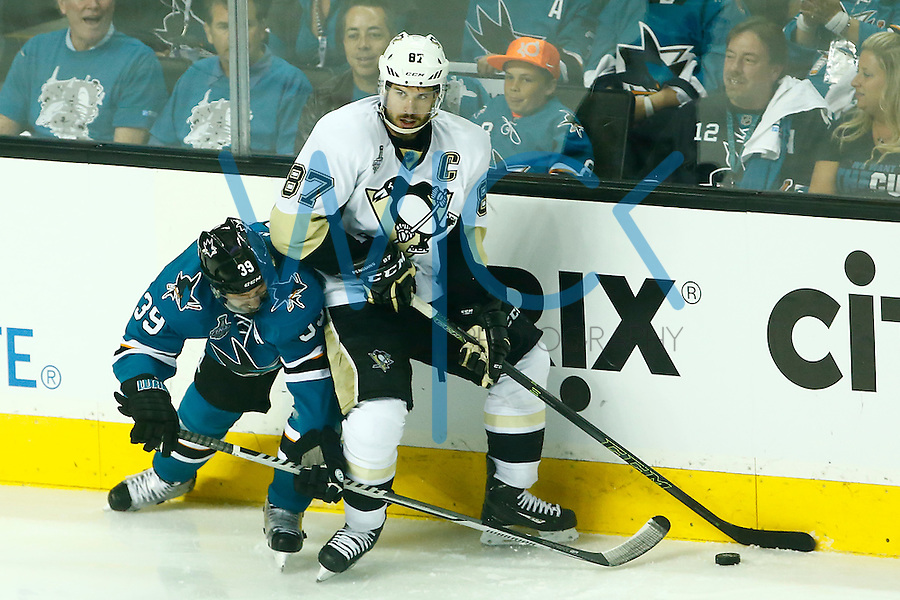 Sidney Crosby #87 of the Pittsburgh Penguins carries the puck along the boards in front of Logan Couture #39 of the San Jose Sharks during game three of the Stanley Cup Final at the SAP Center in San Jose, California on June 4, 2016. (Photo by Jared Wickerham / DKPS)