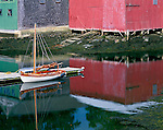 Knox County, ME<br /> Weathered red and green boat houses behind a single wooden sailboat moored in Camden Harbor with receding tide