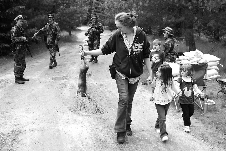 Brandy Hoyt, from Couer d'Alene, Idaho, carries a dead rabbit back to camp after Hoyt shot it with his hand gun in the presence of the their children...Initially they had planned on eating the rabbit with dinner, but soon found out from the battalion medic that it may contain harmful bacterias, and was later discarded.