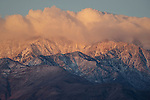 Morning light on a snow covered and clouded-over Telescope Peak in the Panamint Mountains, as seen from Badwater, Death Valley National Park, California