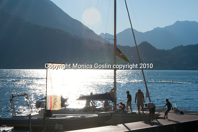 A family docks their boat at Varenna, Italy on Lake Como