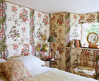 A bower-like atmosphere has been created in this bedroom by hanging the walls in a large-patterned chintz wallpaper with a Roman blind and headboard to match
