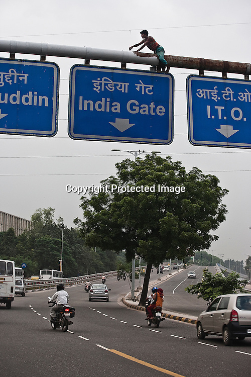 Indian labourers paint the signboard in New Delhi, India.