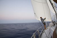 Sailor checking the jib and main sails on a Beneteau yacht