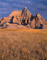 SDBD_036 - USA, South Dakota, Badlands National Park, North Unit, Early morning light defines storm clouds over Vampire Peak and autumn colored grasses.