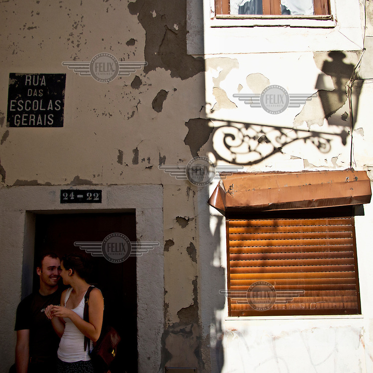 A couple wait for a taxi on a street corner in the historic centre of the city.