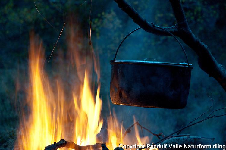 Stor, svart gryte over bålet. ---- Kettle and camp fire.