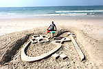 """Palestinian artist Mohammed Totah with amputated leg, poses in front a sand sculpture reads in Arabic """"my mother"""" to mark the Mother's Day, at the beach of Gaza city on March 21, 2019. Totah, 31 year-old, who had lost his leg during the Israeli war on Gaza Strip in 2008, despite his disability, he succeeded in writing and drawing sculptures by sand on the Gaza beach marking the national events. Photo by Mahmoud Ajjour"""