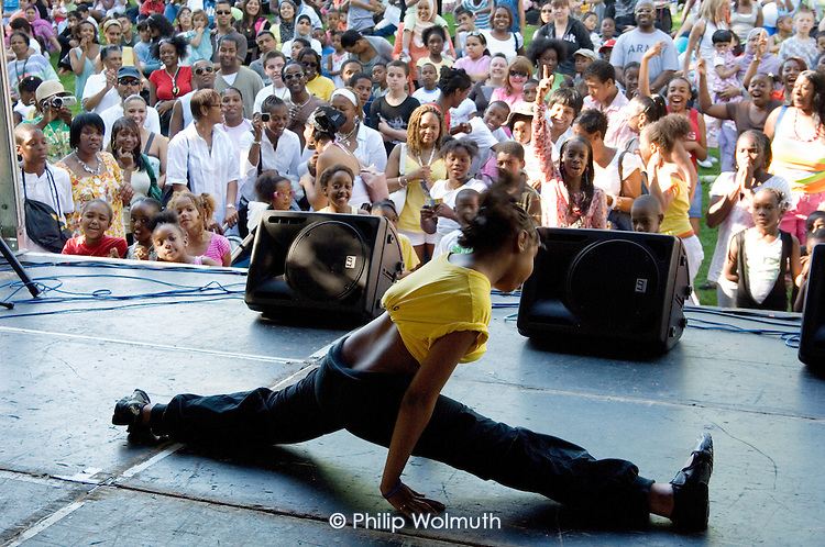 A crowd of local residents watch Silent Steps dance group perform at Queens Park Gardens summer festival, West London.