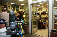 Steve and Teresa Mallory sit on a sofa just inside the door of their store on Newport Avenue in Ocean Beach as a film crew work outside Friday night April 11, 2008.  Parts of OB have been taken over by the crew who are filming a pilot of a new CBS show called Mythological X over the past few days.