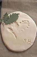 Kinder basteln Blattkacheln aus Salzteig, Salzteig mit Abdruck vom Eichenblatt auf Backblech zum Brennen