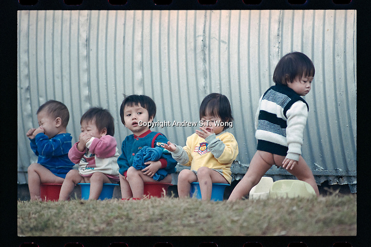 Vietnamese refugee toddlers undergo potty training at a boat people camp in Hong Kong. Tens of thousands of Vietnamese refugees fled the Communist regime by boats to Hong Kong in 1980s.