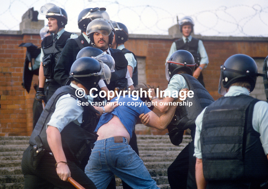 Policemen in riot gear move in among football fans to keep the peace at a friendly pre-season match between Cliftonville FC and visitors, Glasgow Celtic. 19840098b..Copyright Image from Victor Patterson, 54 Dorchester Park, Belfast, UK, BT9 6RJ..Tel: +44 28 9066 1296.Mob: +44 7802 353836.Voicemail +44 20 8816 7153.Skype: victorpattersonbelfast.Email: Email: victor@victorpatterson.com.<br />