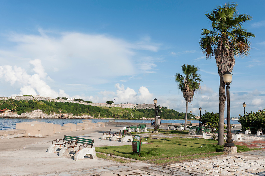 Havana, Cuba; park benches line the walkway between the entrance to Havana Harbor and Avenida del Puerto, with the Fortaleza de San Carlos de la Cabana visible on the hill across the channel