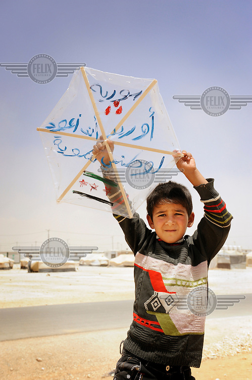 Syrian refugee Hamzeh holds up a kite he has made himself. On the kite he has written a message of peace for his country. 'I want to return to my country' is Hamzeh's message. He misses the comfort of his old life before the conflict and tells the world, 'I want my home back, here is not my home, there is just sand and I have to wait in line for everything.' /Felix Features