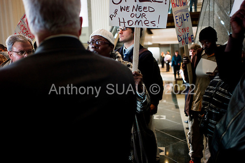 Philadelphia, Pennsylvania<br /> March 24, 2011<br /> <br /> Demonstrators in the entrance hall of the U.S. Department of Housing and Urban Development's (HUD) regional office in the Wanamaker Building confront HUD employee (man with white hair) demanding immediate implementation of the EHLP program, a $1 billion program enacted by Congress to assist homeowners and to prevent foreclosure. EHLP funds, to be obligated by September 30, 2011, are to provide mortgage payment assistance of up to 24 months to homeowners who have had at least 14% drop in income due to involuntary unemployment or underemployment caused by adverse economic conditions, medical emergency or serious injury.<br /> <br /> Philadelphia Unemployment Project (PUP) organized the rally.
