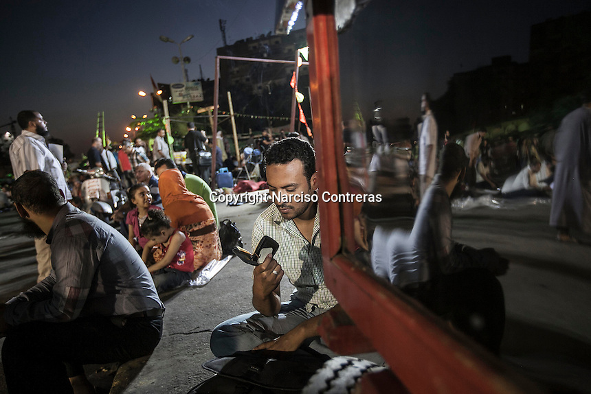 "In this Wednesday, Jul. 10, 2013 photo, a supporter of the ousted president Mohammed Morsi reads a printed version of the Quran instants at the dusk before to break the festing ""Iftar"" in the streets nearby Al-Rabba Alawya mosque during the first day of the holy month of Ramadan in Cairo, Egypt. (Photo/Narciso Contreras)."
