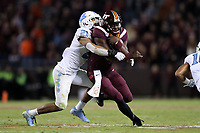 BLACKSBURG, VA - OCTOBER 19: Quincy Patterson II #4 of Virginia Tech is tackled by Chazz Surratt #21 of the University of North Carolina during a game between North Carolina and Virginia Tech at Lane Stadium on October 19, 2019 in Blacksburg, Virginia.