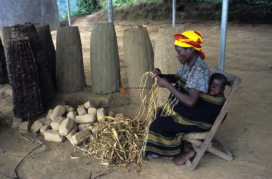 Pigmy woman weaving rope. Improved beehives in the background