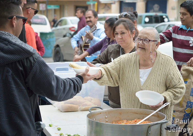 "Maria Natividad Granados, a Methodist woman in Nuevo Laredo, Mexico, serves food to Cuban immigrants in that city's Plaza Benito Juarez on March 3, 2017. Hundreds of Cubans are stuck in the border city, caught in limbo by the elimination in January of the infamous ""wet foot, dry foot"" policy of the United States. They are not allowed to enter the U.S. yet don't want to return to Cuba. Many of the city's churches have become temporary shelters for the immigrants, and congregations rotate responsibility for feeding the Cubans, who have slowly been forced to appreciate Mexican cuisine. Such solidarity from ordinary Mexicans is being tested these days, as not only are the Cubans stuck at the border, but the U.S. has stepped up deportations of Mexican nationals, while at the same time detaining many undocumented workers from other nations and simply dumping them on the US-Mexico border. Granados is a member of the El Ebenezer Methodist Church in Nuevo Laredo."
