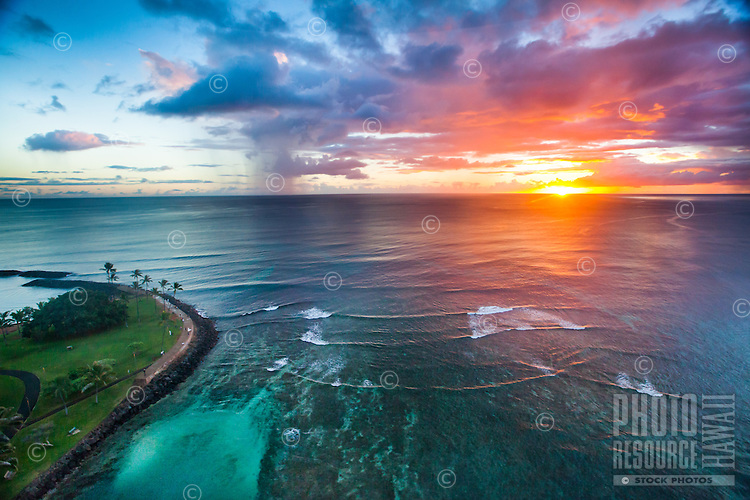 A colorful sunset is reflected in the waves and over the reef near Magic Island, Honolulu, O'ahu.
