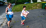 WATERBURY , CT-080720JS09—Heather Britton, a member of the Waterbury Sister Wine Fairies, along with help from her son Isaiah Hernandez, 8, delivers homemade gift baskets to a Waterbury resident on North Walnut Street on Friday. <br /> Jim Shannon Republican-American