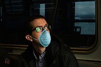 NEW YORK, NEW YORK - MARCH 03 : A man wears a face mask as he rides the air train inside the John F. Kennedy International Airport in New York on March 03, 2020. New York confirms second coronavirus case, as flights cancelations and Jewish schools close over virus fears.The first person to test positive for coronavirus in the state is a 39-year-old health-care worker who arrived from Iran with her husband, the second one is an attorney who lives in Westchester County, works in Manhattan, Gov. Andrew Cuomo said. (Photo by Eduardo Munoz / VIEWpress via Getty Images)