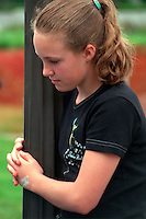 Thoughtful girl age 12 at Vietnam Wall on Memorial Day. St Paul Minnesota USA