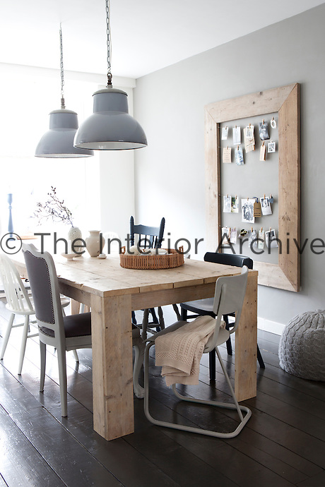 Grey and natural tones influence the decoration of the dining room, teamed with a subtle industrial feel reinforced by the salvaged dining table and a pair of second-hand pendant lamps