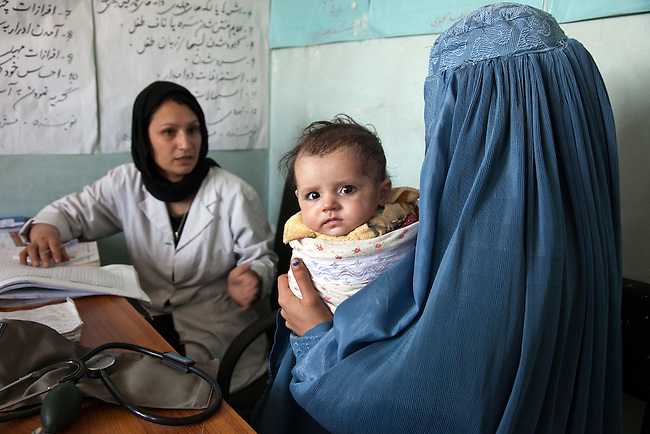 """10 May 2012, Tajikhan Village, Jabalseraj District Parwan Province, Afghanistan : Muzhda Malikzada (29) a mid wife at the Sar-e-Hause medical health clinic speaks with twenty two year old Soraya (burqa) and 5 month old baby Zainab..Muzhda trained during the Taliban days and one  of a very few women in her village allowed out of the house to do her work. """"We had fireworks every day."""" she says..The clinic is funded by the Strengthening Health Activities for Rural Poor Project (SHARP). SHARP aims to improve the health and nutrition status of Afghans, focusing especially on women and children and the underserved areas of the country. Already remarkable progress has been made in the reduction of infant and under five mortality as well as pregnancy related mortality. With World Bank support in 11 provinces the number of health clinics has nearly tripled from 148 to 432 and about 85% of the population now lives in districts which now have service providers to deliver a basic package of health service.  The project supports Afghanistan's Health and Nutrition Sector Strategy  which is the governments blueprint for the health sector program for the period 2008-13. Picture by Graham Crouch/World Bank"""