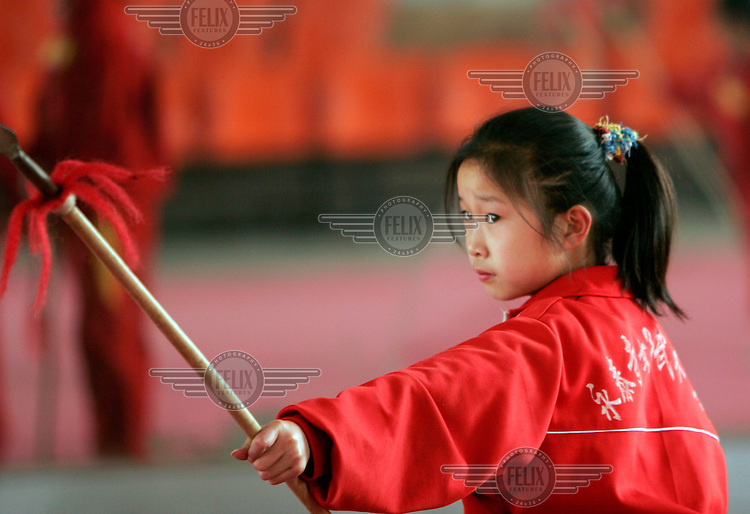 A young martial artist trains with a spear at the Yongtai Women's Martial Arts School, the only all-female martial arts centre in China....
