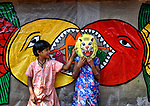 Children play around with a colorful mask in a village full of artistic familes who specialise in making all kinds of handcrafts.  The kids are pictured in front of a decorated wall in the Naya village of Pingla, India.<br /> <br /> Each year the village holds a fair putting their handcrafted artworks on display for tourist and Avishek Das, 35, from Kolkata, India was there to witness it.<br /> 