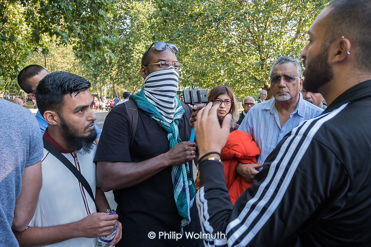 A masked man uses a smartphone to video his opponent during an argument at Speakers' Corner, Hyde Park, London.
