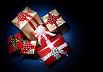 Pile of Christmas gift boxes illuminated in darkness isolated on dark blue background