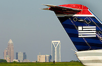 A US Airways plane on the runway of Charlotte-Douglas International Airport in Charlotte, North Carolina. The downtown Charlotte skyline is in the background. Charlotte-based photographer has other images of transportation, airplanes on runways (and taking off and landing) and interior/exterior airport images of Charlotte-Douglas Intl Airport in portfolio.