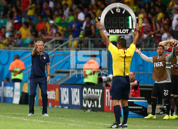 USA coach Juergen Klinsmann rages at the fourth official as he holds up the board to signal only one minute of added time in the second period of extra time
