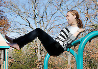 NWA Democrat-Gazette/DAVID GOTTSCHALK  Morrigan (cq) White, 13, attempts to a swing to new heights Monday, November 23, 2015, at Walker Park in Fayetteville. Morrigan (cq) was swinging with Aquene (cq) Howell, 12. The two Fayetteville Public School students are out of school this week because of the Thanksgiving Holiday.