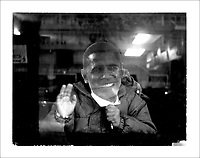 Omar Bah,  6, waives from behind an Obama mask out the window of his parents' restaurant and club near Howard University.  The Bahs are a family of immigrants from Guinea and Morocco.  Inauguration.  Photographs from around DC including Adam's Morgan, U-Street, and Howard University.  For many, U-Street is regarded as the soul of DC, a traditionally black part of town cutting through the the northern quadrants of the Capital.
